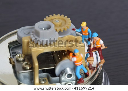 Selective focus of miniature engineer and worker to fixed and repair musical box and use for business background. - stock photo