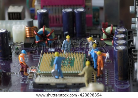 Selective focus of miniature engineer worker to fixed and repair Control Processing Unit (CPU) processor,  mainboard computer background as technology concept. - stock photo