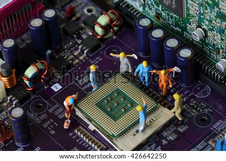 Selective focus of miniature engineer worker to fixed and repair Control Processing Unit (CPU),  mainboard computer and use for industry background.
