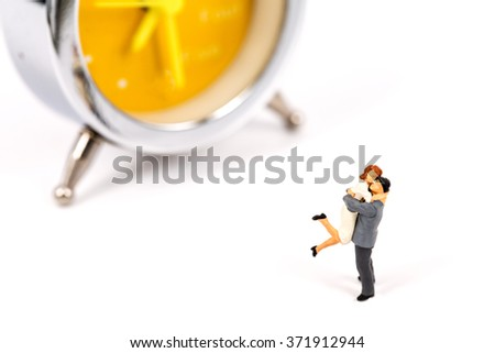 selective focus of miniature lover couple with clock on white background ,abstract background to time management. - stock photo