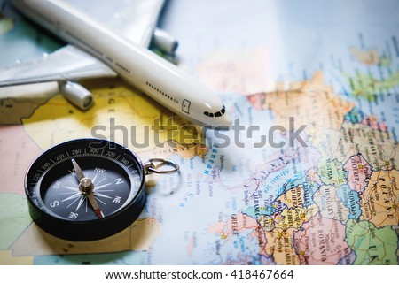 selective focus of miniature tourist on compass over map with plastic toy airplane,abstract background to travel concept. - stock photo