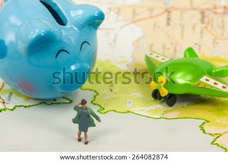 selective focus of miniature tourist over map with piggy bank and plastic toy airplane,abstract background to saving money for travel concept - stock photo