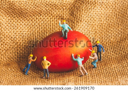selective focus of miniature worker people sitting on egg , abstract background to happy easter holiday concept. - stock photo