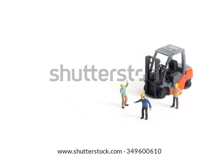 selective focus of miniature worker standing front of forklift machine, isolated on white. - stock photo