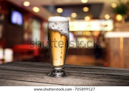 selective focus of mug of beer standing on wooden table in bar