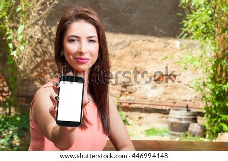 Selective focus of pretty lady holding smartphone with blank screen on an outdoor terrace - stock photo