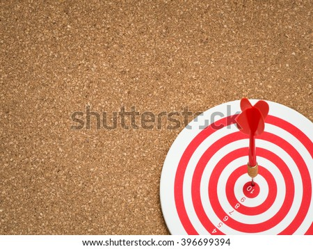 Selective focus of red dart arrow hitting target center of dartboard on cork board background. Bullseye and Dart. Success/fail business concept. Success hitting target aim goal achievement concept. - stock photo
