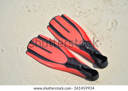 Selective focus of red diving fins on sand beach