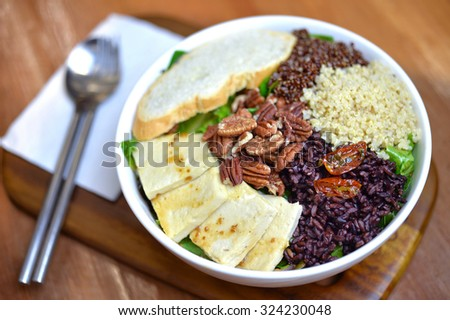 Selective focus of Salad bowl with tofu, riceberry, garlic bread and quinoa and Japanese dressing style - stock photo