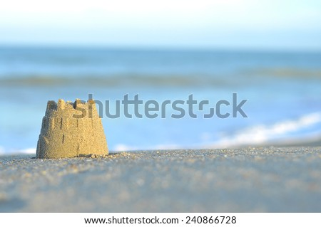 Selective focus of sand castle at the beach and copyspace area - stock photo