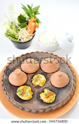 Selective focus of steam fish curry in stone pan on white background, Thai food - stock photo