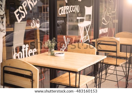 selective focus of table of coffee shop outside view with vintage color tone