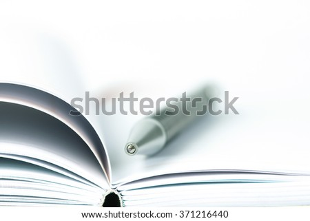selective focus of the ball pen on opened lined diary book - stock photo