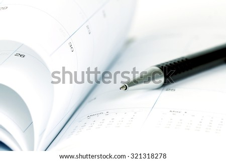 selective focus of the ball pen on opened lined diary book with calendar page