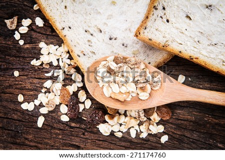 selective focus of the cereal and black sesame bread and whole grain cereal flakes which mixed warming cinnamon , red skin apple , golden raisins and roasted hazelnuts on wooden plate - stock photo
