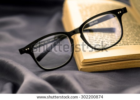 selective focus of  the reading Eyeglasses with opened book on grey silky fabric - stock photo