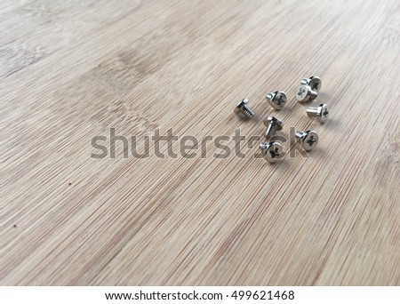 Selective focus of tiny screws on a wooden table