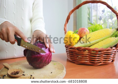 Selective focus of Young woman cutting cauliflower and vegetable in kitchen table