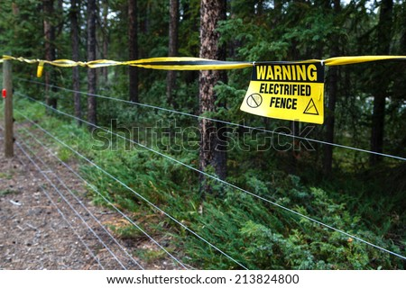 Selective focus on an electrified fence warning sign at a camping site to keep out bears in the wild. - stock photo