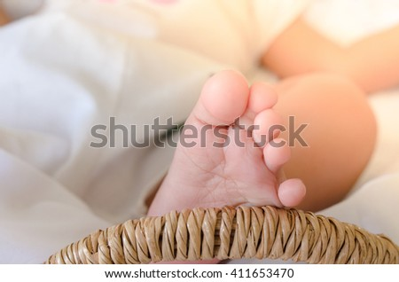 Selective focus on baby's feet, baby girl in a basket with light leak.  - stock photo