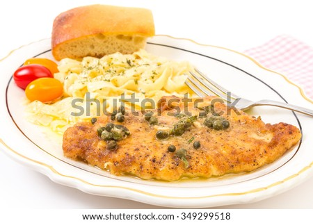 Selective focus on Breaded chicken breast baked to a golden brown in lemon garlic butter topped with capers.  Served with pasta garnished with parsley.  Horizontal on white background with copy space. - stock photo
