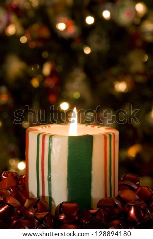Selective focus on candy striped candle in front of the Christmas Tree with soft focus.