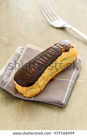 Selective focus on chocolate eclair on the napkin fold on the grunge table.