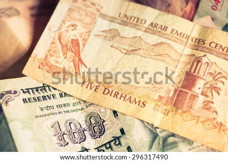 Selective focus on currencies of United Arab Emirates and Republic of India - stock photo