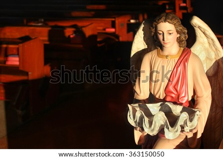Selective focus on faces baptistery  angel statue / Evening light shining faces baptistery  angel statue holding a basin -shaped shells stripper in church - stock photo