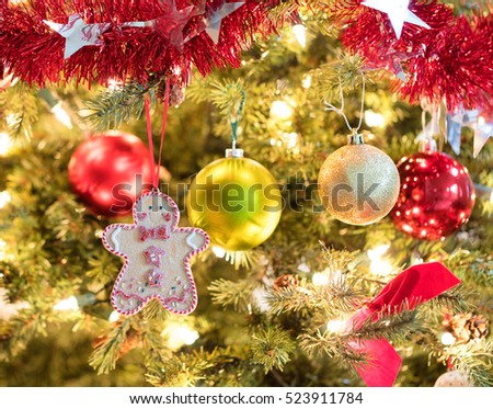 Selective focus on hanging holiday cookie in fully decorated Christmas tree.