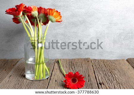 Selective Focus on Red Gerbera :  Red Gerbera beside the Jar on wood Background
