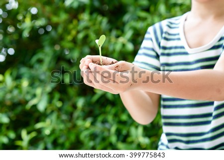 Selective focus on small kid hand holding young seedling plant in soil for growing. Earth day concept.