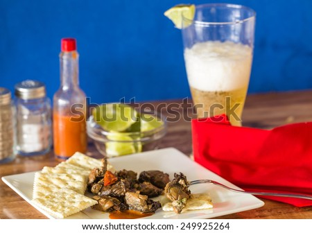 Selective focus on smoked oyster packed with chopped red peppers on saltine crackers and hot sauce.  Served with glass of beer as Happy Hour Snack. - stock photo