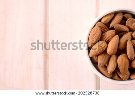 Selective focus on the almonds in the cup and blank space on left side