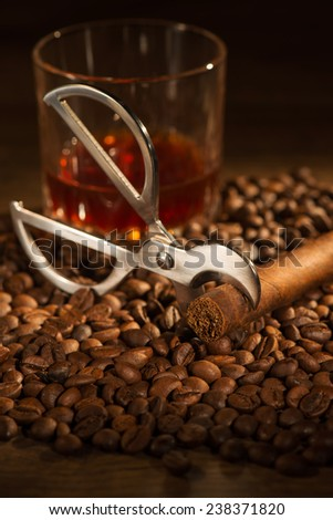 Selective focus on the Cuban cigar and cutter lying on the heap of coffee beans. Glass of whiskey on background