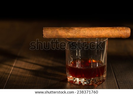 Selective focus on the Cuban cigar lying on the glass of whiskey that standing on the wooden table - stock photo