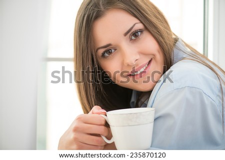 Selective focus on the dark-haired beautiful smiling girl waking up in the morning wearing blue pajamas sitting at the windowsill looking at us holding a cup of hot delicious coffee