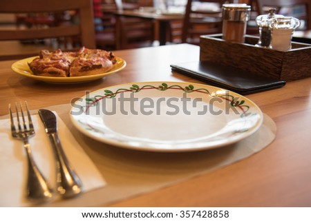 Selective Focus On The Dish On Restaurant Wooden Table With Tableware, Seasoning Bottles - stock photo