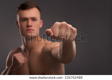 Selective focus on the fist of young handsome fair-haired bare-chested karate enthusiast coaching himself before the important fight