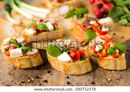 Selective focus on the fresh baked bruschetta with cheese and vegetables in the middle  - stock photo