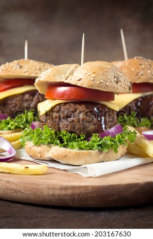 Selective focus on the front cheeseburger on wooden background  - stock photo