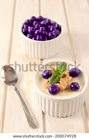Selective focus on the front cup stuffed with blueberries,cereal and yogurt  - stock photo