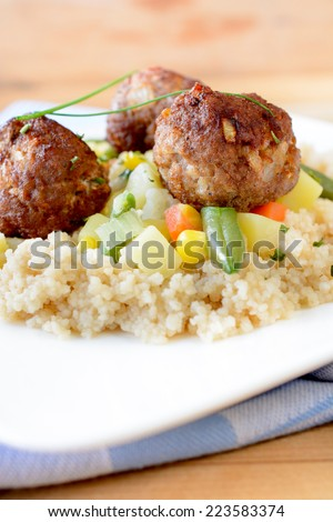 Selective focus on the front meatball with couscous and vegetables  - stock photo