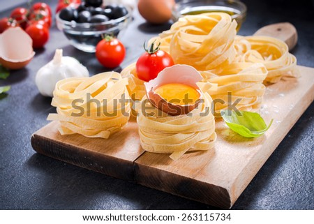 Selective focus on the front pasta with eggs,ingredients in background - stock photo