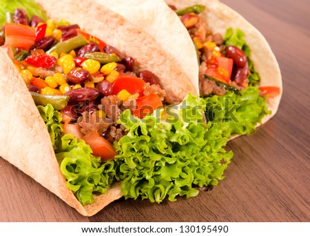 Selective focus on the front taco sandwich on wooden background