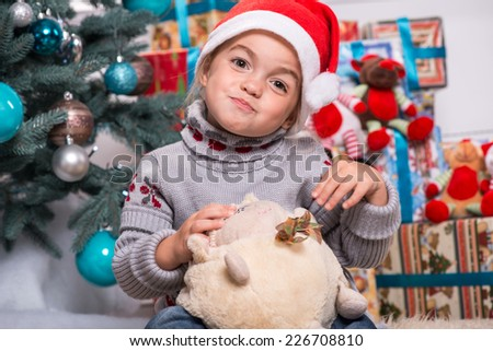 Selective focus on the little cute fair-haired smiling girl sitting on the floor near Christmas presents wearing warm sweater and red cap of Santa Claus playing with the round soft toy - stock photo