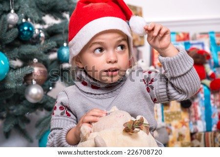 Selective focus on the little cute fair-haired surprised girl sitting on the floor near Christmas presents wearing warm sweater and red cap of Santa Claus playing with the round soft toy - stock photo