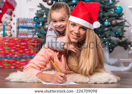 Selective focus on the little cute girl sitting on her happy smiling mom writing a letter for Santa Claus - stock photo