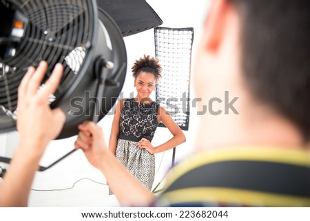 Selective focus on the lovely smiling African model wearing wonderful evening dress standing in front of projectors looking at the photographer - stock photo