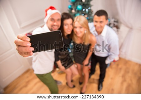 Selective focus on the phone in the hands of smiling guy making photo of his friends standing near the decorated New Year tree on background. Top view - stock photo